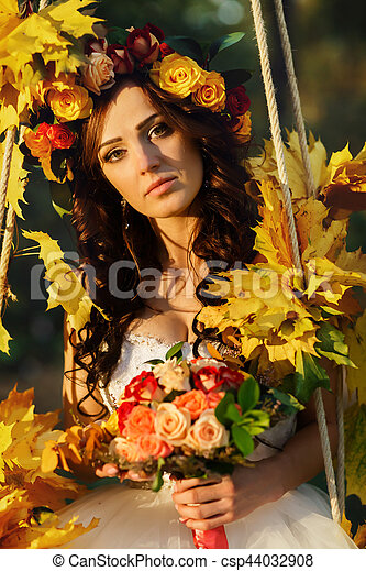 A portrait of a bride sitting on the swing decorated with golden autumn leaves - csp44032908