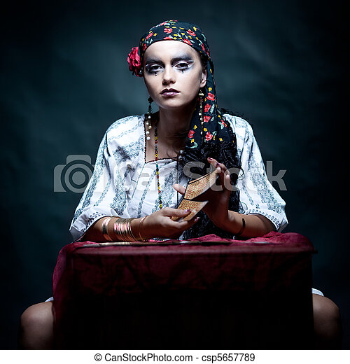 a portrait of a gypsy fortune teller mixing the tarot cards. - csp5657789