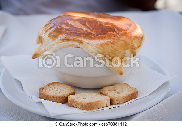 A pot of soup and a lid of bread. - csp70381412