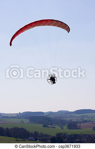 A powered paraglider pilot in flight over the landscape - csp3671933