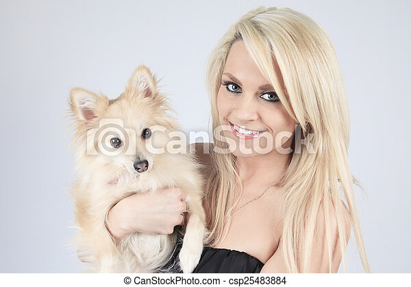 A pretty blond girl sitting with is dog on the sofa - csp25483884