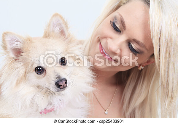 A pretty blond girl sitting with is dog on the sofa - csp25483901