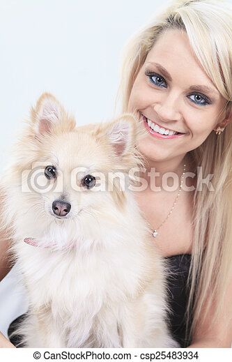 A pretty blond girl sitting with is dog on the sofa - csp25483934