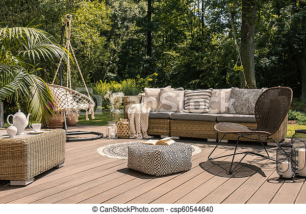 A rattan patio set including a sofa, a table and a chair on a wooden deck in the sunny garden. - csp60544640