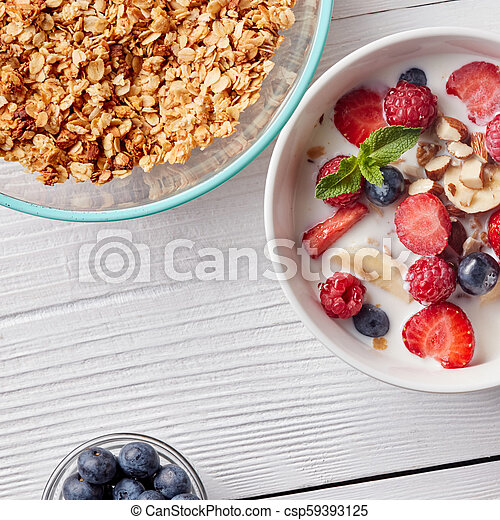 A ready breakfast of natural organic ingredients - granola, berries, nuts, honey, milk for the preparation of natural healthy food on white table. - csp59393125