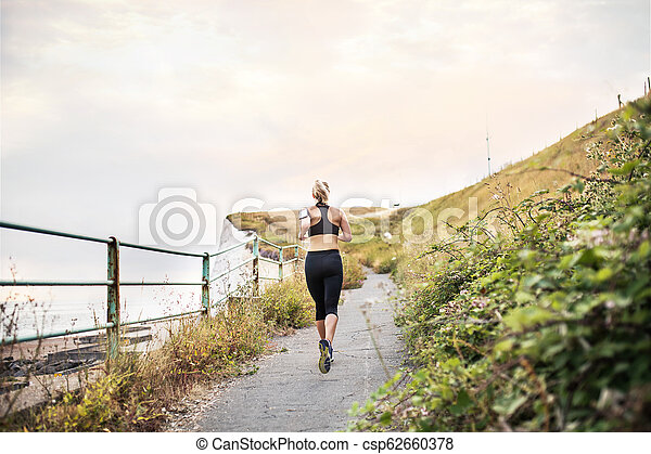 A rear view of young sporty woman runner running by sea in nature. - csp62660378