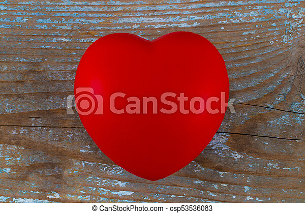 A red heart on the wooden background - csp53536083