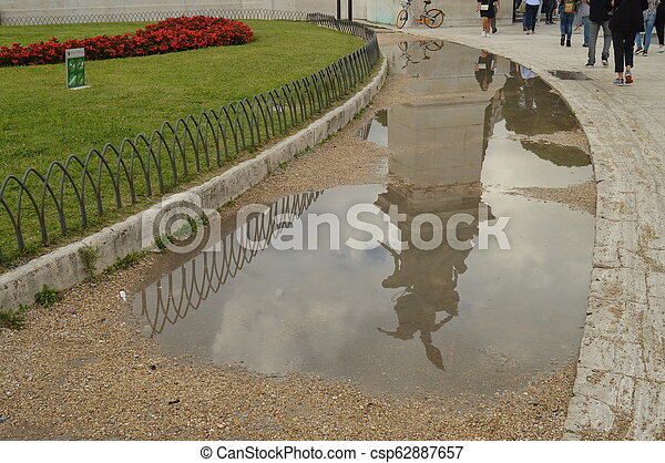 A reflection in a puddle after the rain Statue in the Vittoriano monument of Vittorio Emanuele II in Rome, Italy on October 07, 2018 - csp62887657