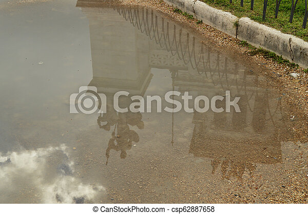 A reflection in a puddle after the rain Statue in the Vittoriano monument of Vittorio Emanuele II in Rome, Italy on October 07, 2018 - csp62887658