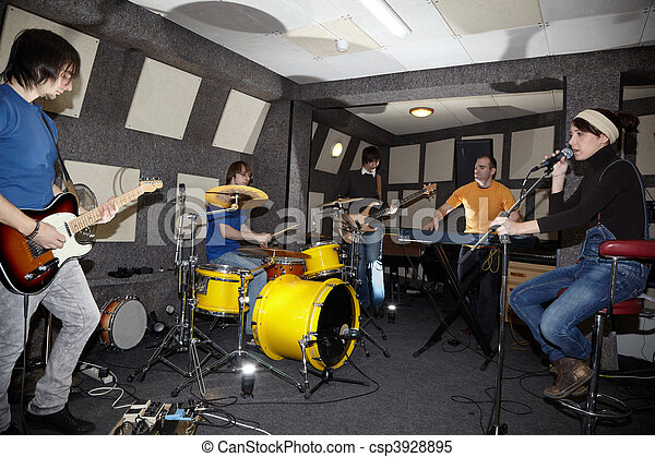 a rock band. vocalist girl, two musicians with electro guitars, keyboarder and one drummer working in studio. flashes in center - csp3928895