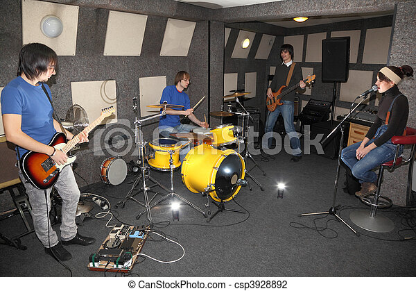 a rock band. vocalist girl, two musicians with electro guitars and one drummer working in studio. flashes in center - csp3928892