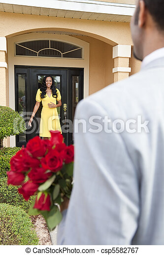 A romantic African American man bringing flowers to his happy wife or girlfriend who is standing waiting for him at the door of their home. - csp5582767