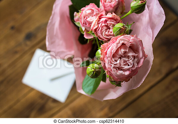 a roses with envelope on wooden background - csp62314410