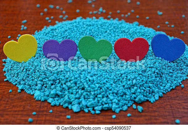 a row of colored hearts on blue sand on a red table - csp54090537