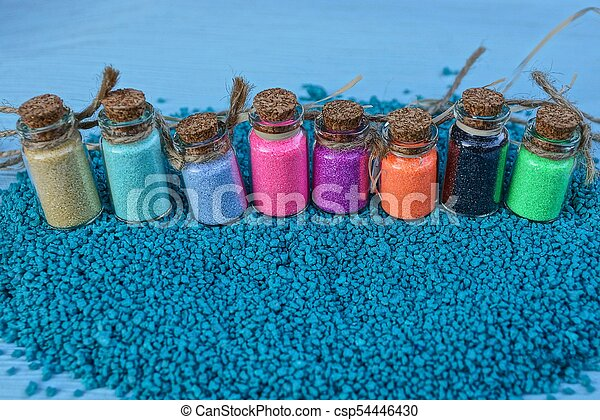 a row of glass bottles with colored sand - csp54446430