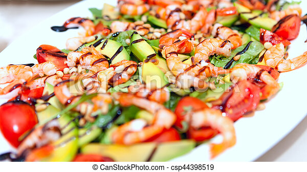 A salad dish with prawns, avocado, seafood, tomatoes in a white dish - csp44398519