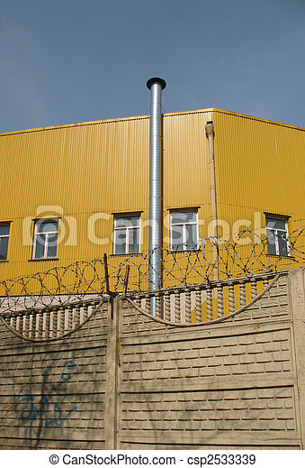 A secured industrial zone with concrete fence, barbed wire and brick chimney-stalk on the blue sky background. - csp2533339