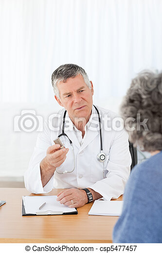 A senior doctor talking with his patient - csp5477457
