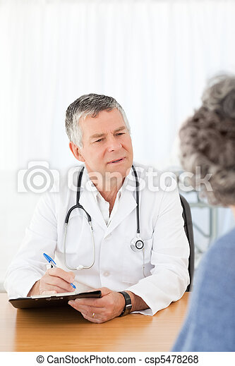 A senior doctor talking with his patient - csp5478268
