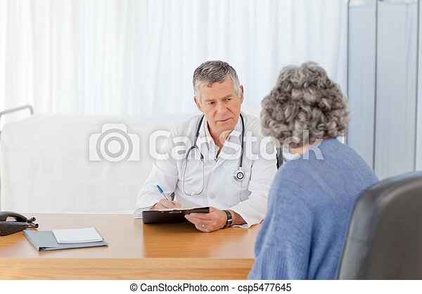 A senior doctor talking with his patient - csp5477645