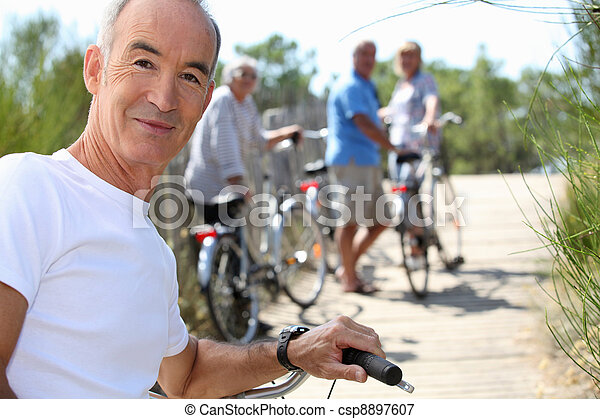 a senior man doing bike with friends in summer - csp8897607