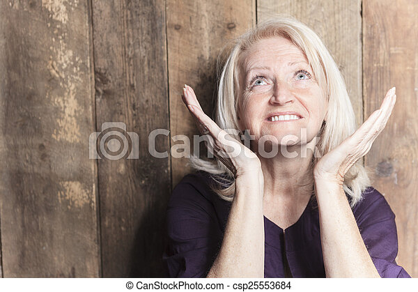 A senior woman pray with a wood background - csp25553684