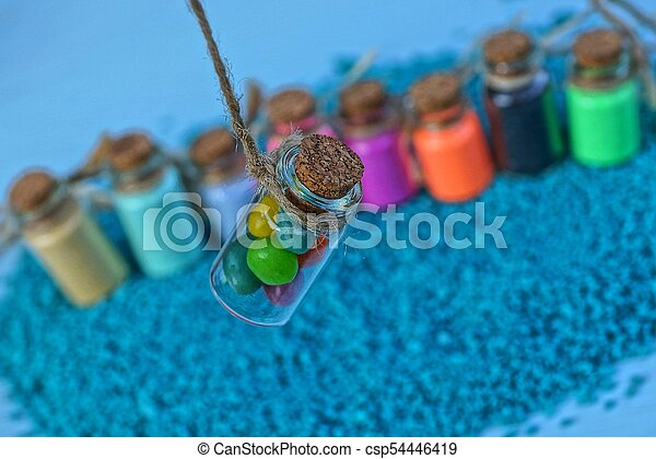a set of small colored bottles with sand - csp54446419