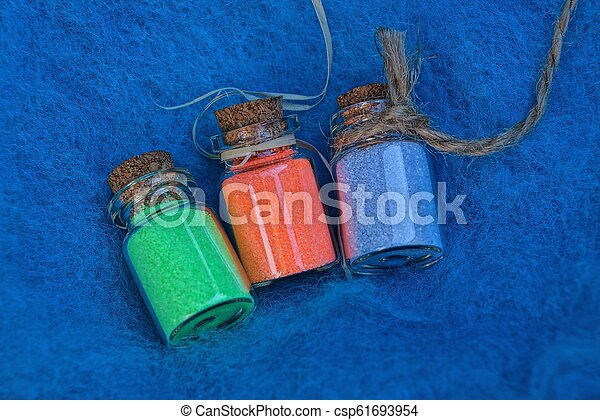 a set of small glass decorative bottles with colored sand on a blue wool fabric - csp61693954