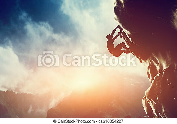 A silhouette of man climbing on rock, mountain at sunset.  - csp18854227