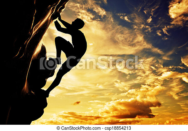 A silhouette of man free climbing on rock, mountain at sunset. Adrenaline, bravery, leader. - csp18854213