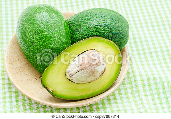 A sliced avocado in wooden dish. - csp37887314