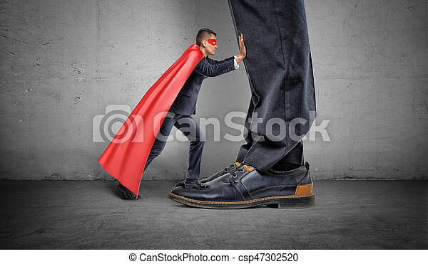 A small businessman in a superhero cape trying to push away giant man legs. - csp47302520