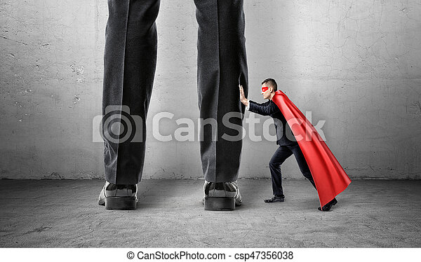 A small businessman in a superman cape trying to push away giant man legs. - csp47356038
