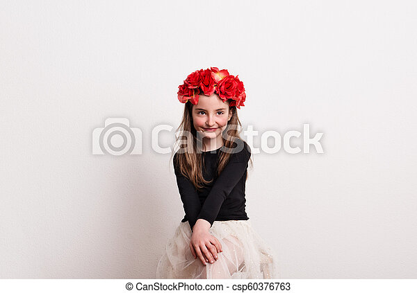 A small girl with flower headband sitting in a studio, hands on her knees. - csp60376763