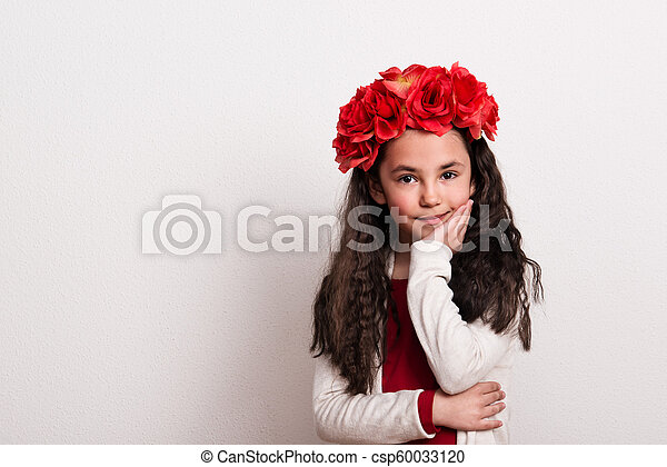 A small girl with flower headband standing in a studio, chin resting on her hand. - csp60033120