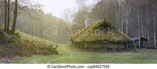 A small house in the forest surrounded by trees in autumn - csp84537559