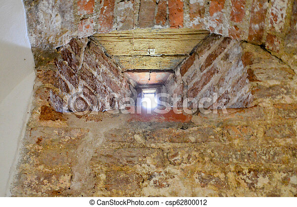 A small narrow window on an old, ancient, cracked stone shabby brick wall of red brick in the basement. The background - csp62800012
