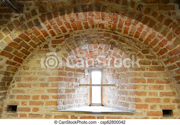 A small narrow window on an old, ancient, cracked stone shabby brick wall of red brick in the basement. The background - csp62800042