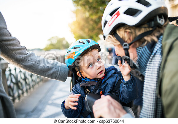 cheap price new specials attractive price A small toddler boy with helmet and young parents outdoors in city ...