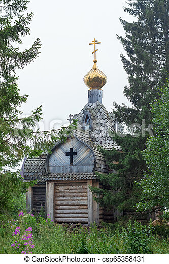 a small wooden chapel in the forest with a golden dome on the shore of Lake Zyuratkul, Ural, Russia - csp65358431