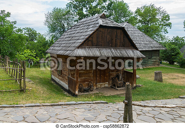 A small wooden house surrounded by a wicker small fence - csp58862872