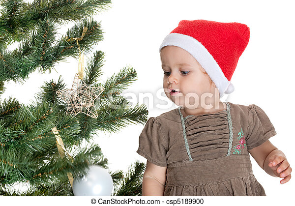 A smiling little girl is decorating a christmas tree; isolated on the white background - csp5189900