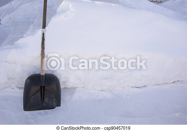 A snow shovel stands against a high snowdrift. Snow removal around the house. There is a lot of snow in the garden in winter. - csp90457019