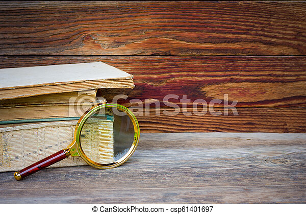 a stack of old books and magnifier on wooden background with space for text - csp61401697
