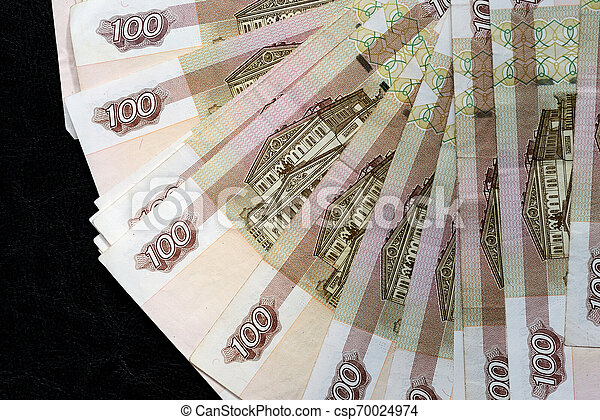 A stack of Russian banknotes of a hundred rubles on a dark background close up - csp70024974