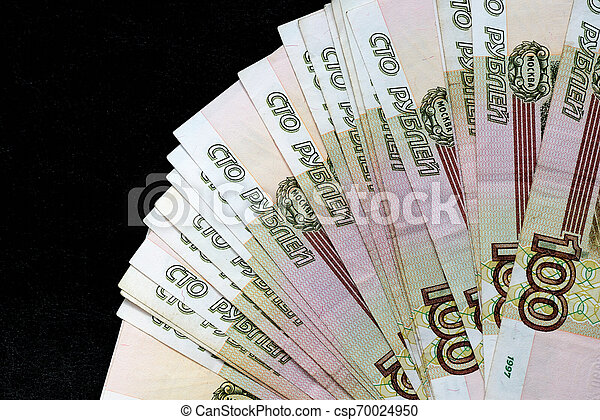 A stack of Russian banknotes of a hundred rubles on a dark background close up - csp70024950