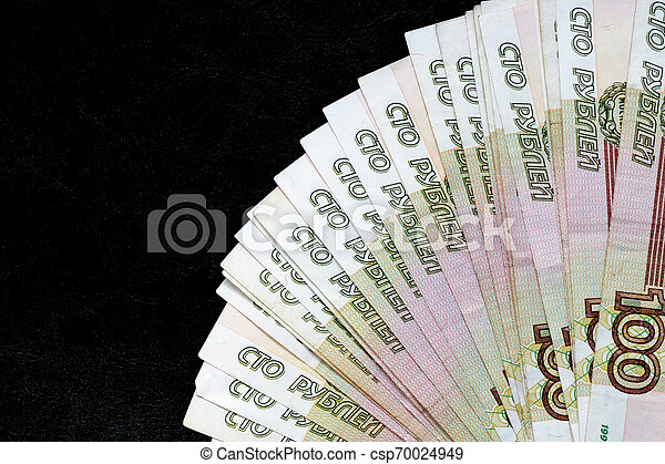 A stack of Russian banknotes of a hundred rubles on a dark background close up - csp70024949