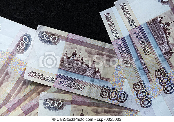 A stack of Russian banknotes of five hundred rubles on a dark background close up - csp70025003