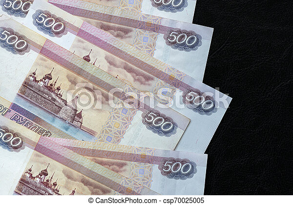 A stack of Russian banknotes of five hundred rubles on a dark background close up - csp70025005