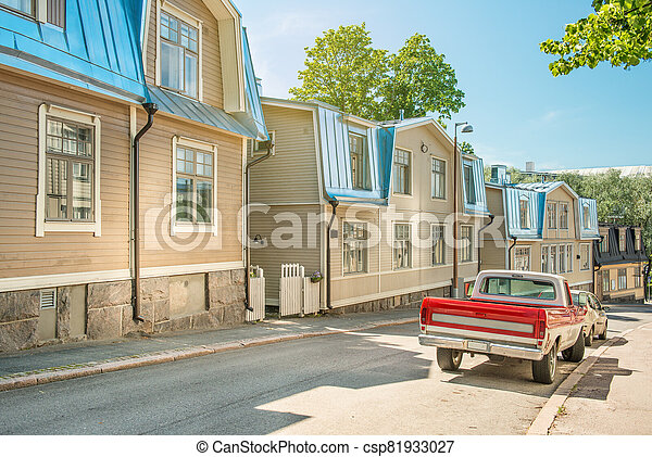 A street in Helsinki on a sunny summer day. Traditional finnish wooden houses in a quiet cozy street, Finland - csp81933027
